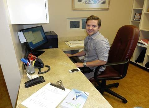 Adam Densley works to set up the front office of the clinic.